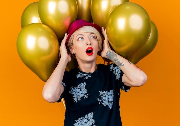 Schockierte junge blonde partyfrau, die partyhut trägt, der vor ballons steht, die hut suchen, der lokalisiert auf orange wand schaut