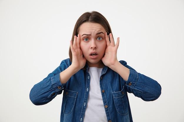 Schockierte junge braunhaarige blauäugige dame ohne make-up, die ihr gesicht mit erhobenen händen hält, während sie ängstlich nach vorne schaut, isoliert über weißer wand