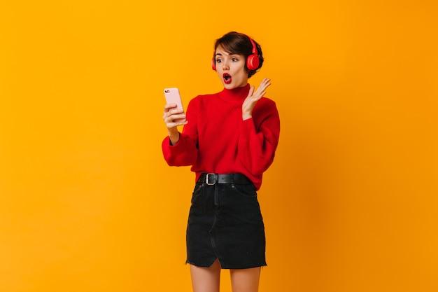 Schockierte junge dame im schwarzen rock, der smartphone betrachtet