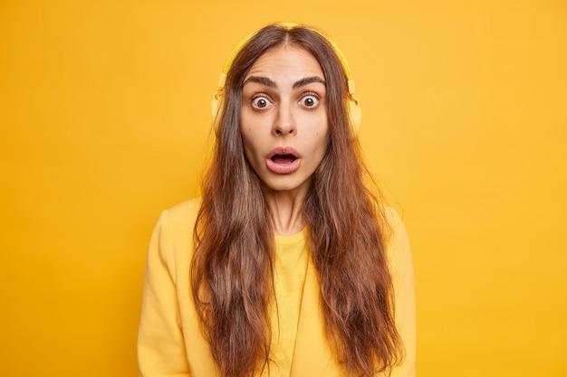 Schockierte junge europäerin mit langen dunklen haaren keucht überrascht steht sprachlos und hält den mund offen
