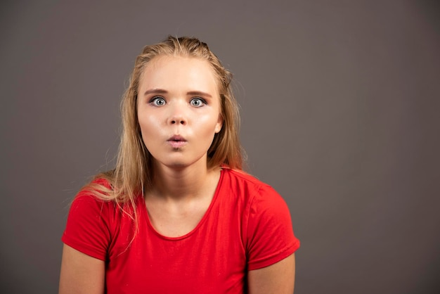 Schockierte junge frau im roten hemd auf dunklem hintergrund. hochwertiges foto