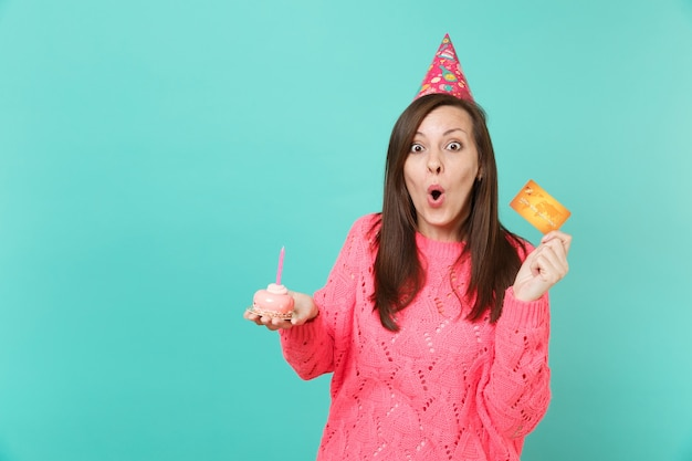 Schockierte junge frau in gestricktem rosa pullover, geburtstagshut, der den mund weit offen hält, kuchen in der hand halten mit kerzenkreditkarte einzeln auf blauem hintergrund. menschen lifestyle-konzept. kopieren sie platz.