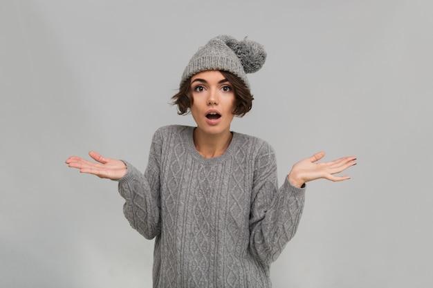 Schockierte junge frau in pullover und warmem hut
