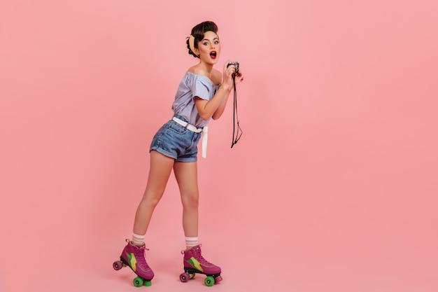Schockierte junge frau in rollschuhen, die auf rosa hintergrund aufwerfen. studioaufnahme des überraschten pinup-mädchens mit kamera.