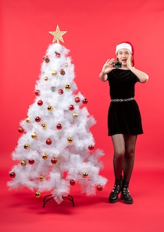 Schockierte junge frau in schwarzem kleid und weihnachtsmannhut, die nahe weißem weihnachtsbaum steht und ihr telefon auf rot hält