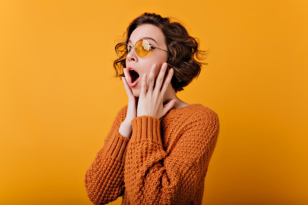 Schockierte junge frau trägt ring und sonnenbrille, die auf gelber wand aufwirft. hübsches dunkelhaariges mädchen in gestrickter kleidung, die erstaunen mit offenem mund und berührendem gesicht ausdrückt.