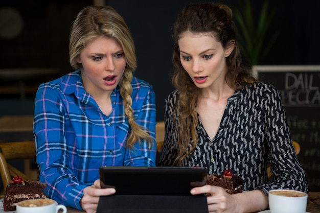 Schockierte junge frauen mit digitaler tablette im café