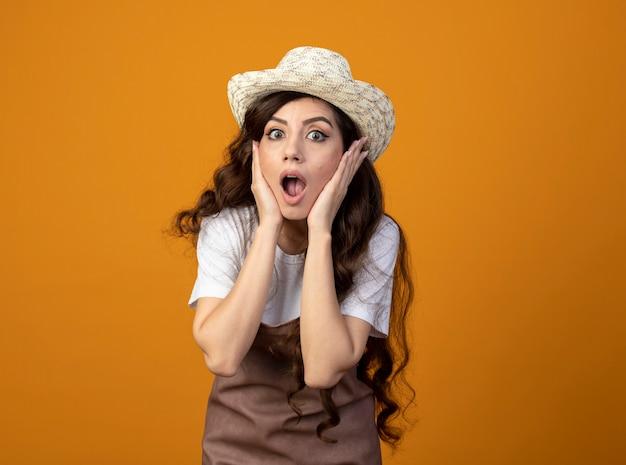 Schockierte junge gärtnerin in uniform, die gartenhut trägt, legt hände auf gesicht lokalisiert auf orange wand mit kopienraum