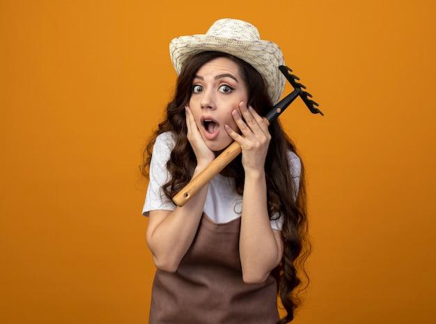 Schockierte junge gärtnerin in uniform, die gartenhut trägt, setzt hände auf gesicht, das rechen lokalisiert auf orange wand hält