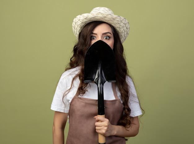 Schockierte junge gärtnerin in uniform mit gartenhut hält und schaut vorne über spaten isoliert auf olivgrüner wand
