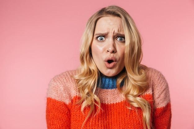 Schockierte junge hübsche schöne frau posiert isoliert über rosa wand