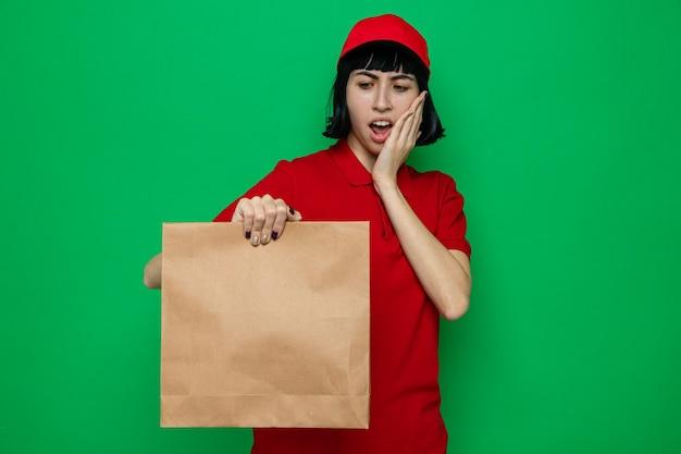 Schockierte junge kaukasische lieferfrau, die papiertüte hält und betrachtet