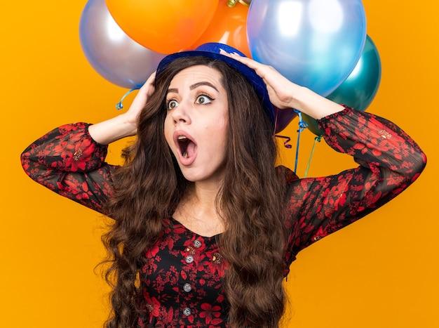 Schockierte junge partyfrau mit partyhut, die vor luftballons steht und die hände auf dem kopf hält und auf die seite isoliert auf der orangefarbenen wand schaut