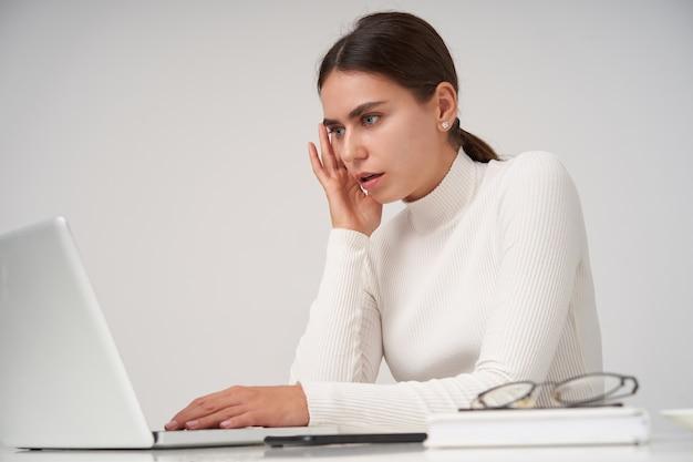 Schockierte junge schöne brünette dame in formellen kleidern, die hand auf tastatur halten und ängstlich auf den bildschirm ihres laptops schauen, über weißer wand sitzend