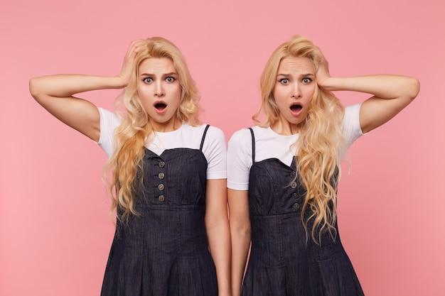 Schockierte junge schöne langhaarige blonde frauen, die erhobene handflächen auf ihren köpfen halten, während sie benommen in die kamera mit weit geöffnetem mund schauen, isoliert über rosa hintergrund