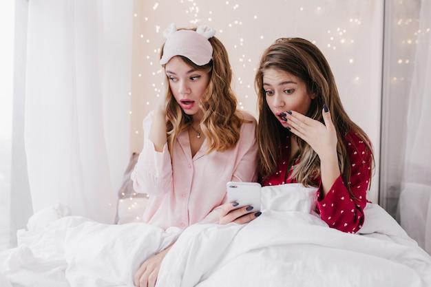 Schockierte langhaarige dame, die unter weißer decke und sms sitzt. innenfoto des gelangweilten blonden mädchens in der rosa schlafmaske.