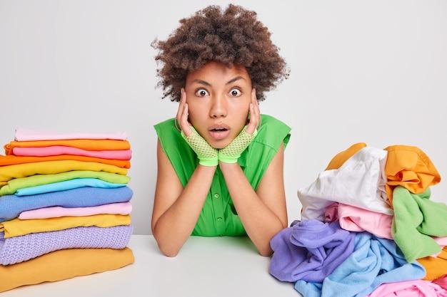 Schockierte, lockige afroamerikanische hausfrau starrt überraschend die hände auf die wangen und kann ihren augen nicht trauen, hat viel hausarbeit gefaltet, gewaschene wäsche isoliert über weiß