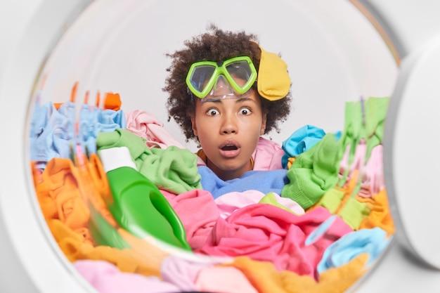 Schockierte lockige frau, die damit beschäftigt ist, zu hause wäsche zu waschen, posiert in der waschmaschine mit schmutziger kleidung und trägt eine schnorchelbrille auf der stirn, die sehr überrascht ist