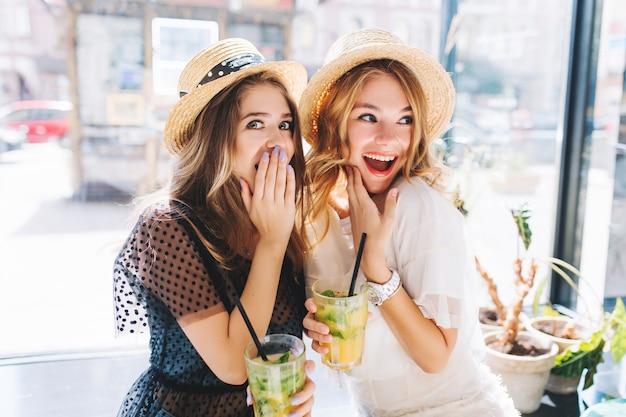 Schockierte mädchen in hüten, die gläser mit cocktail wegschauen und gesichter emotional bedecken