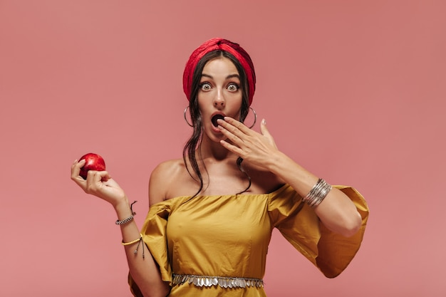 Schockierte modische frau mit coolen accessoires und gelbem kleid, die in die kamera schaut und roten apfel an rosa wand hält