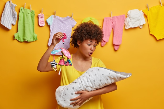 Schockierte mutter kuschelt neugeborenes baby in decke, schaut säugling mit fassungslosem ausdruck an, hält mobiles spielzeug für kinderbett. multitasking mutter, die kleines kind stillt. frauenlebensstil, mutterschaftskonzept.