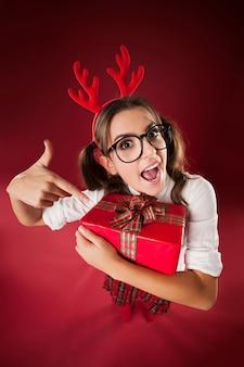 Schockierte nerdige frau, die auf weihnachtsgeschenk zeigt