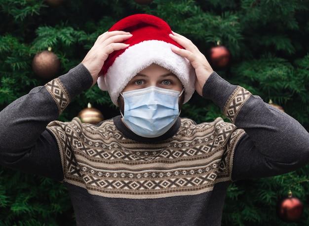 Schockierte oder überraschte weihnachten. schließen sie herauf porträt des mannes, der einen weihnachtsmannhut, weihnachtspullover und medizinische maske mit emotion trägt. vor dem hintergrund eines weihnachtsbaumes. coronavirus pandemie