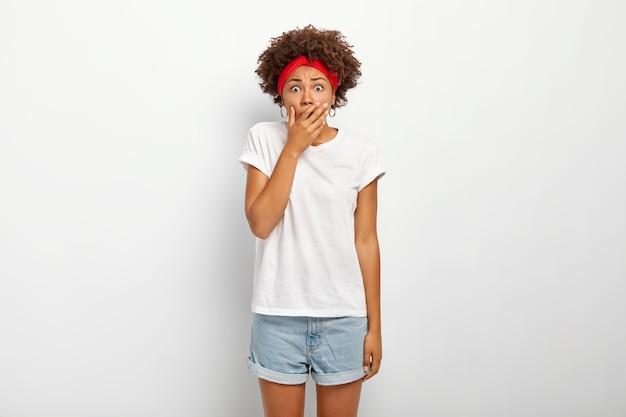 Schockierte panische frau fühlt sich ängstlich und besorgt, bedeckt den mund mit der handfläche