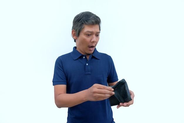 Schockierte reaktion eines mannes, der eine leere brieftasche hält