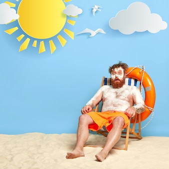 Schockierte rothaarige, die am strand mit sonnencreme aufwirft