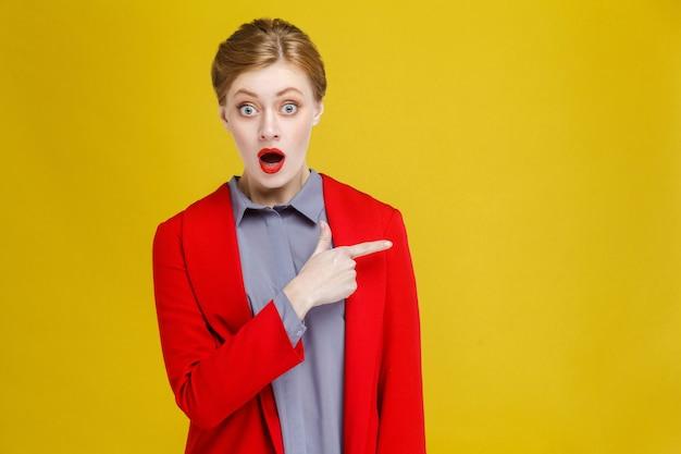 Schockierte rothaarige geschäftsfrau im roten anzug, die am kopienraum zeigt