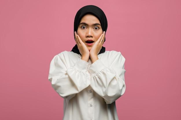 Schockierte schöne asiatische frau, die ein weißes hemd trägt