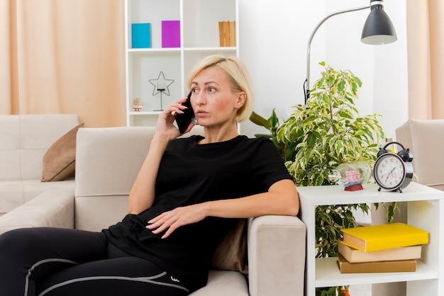 Schockierte schöne blonde russische frau, die auf sessel liegt und am telefon im wohnzimmer spricht