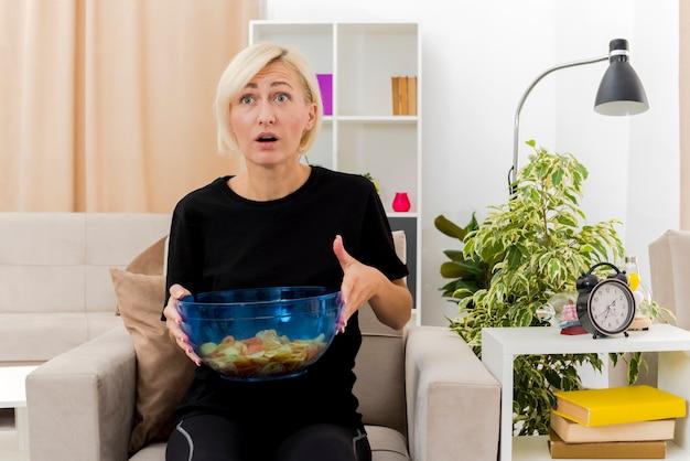 Schockierte schöne blonde russische frau sitzt auf sessel, der schüssel chips hält, die im wohnzimmer nach vorne schauen