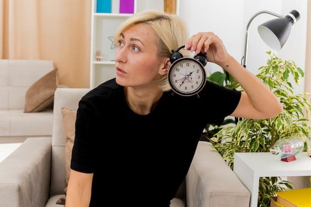 Schockierte schöne blonde russische frau sitzt auf sessel, der wecker hält, der seite innerhalb des wohnzimmers schaut