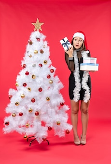 Schockierte schöne frau mit weihnachtsmannhut und stehend in der nähe des geschmückten weihnachtsbaumes