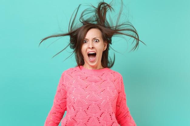 Schockierte schreiende junge frau in gestricktem rosa pullover mit flatternden haaren einzeln auf blautürkisem wandhintergrund, studioporträt. menschen aufrichtige emotionen, lifestyle-konzept. kopieren sie platz.