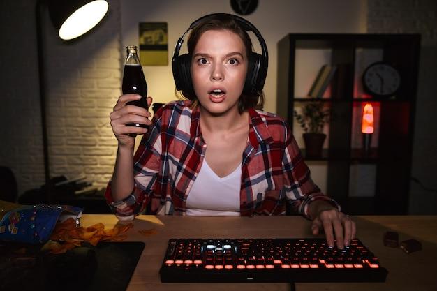 Schockierte spielerin, die am tisch sitzt, online-spiele auf einem computer drinnen spielt und kohlensäurehaltiges getränk trinkt