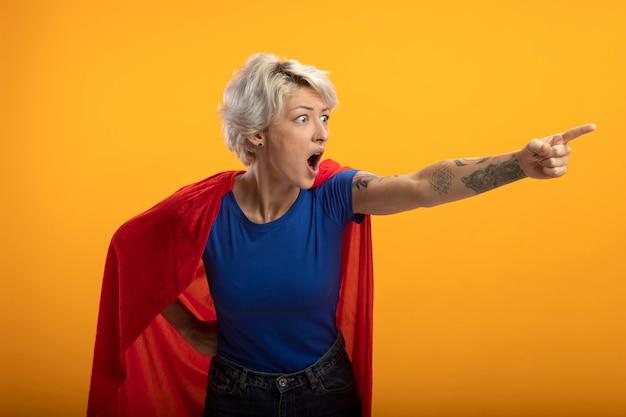 Schockierte superfrau mit rotem umhang sieht und zeigt seitlich isoliert auf orange wand