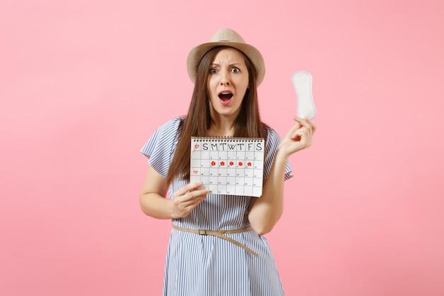 Schockierte traurige frau in blauem kleid, hut mit damenbinde, kalender für weibliche perioden zur überprüfung der menstruationstage einzeln auf rosafarbenem hintergrund. medizin, gesundheitswesen, gynäkologisches konzept. platz kopieren