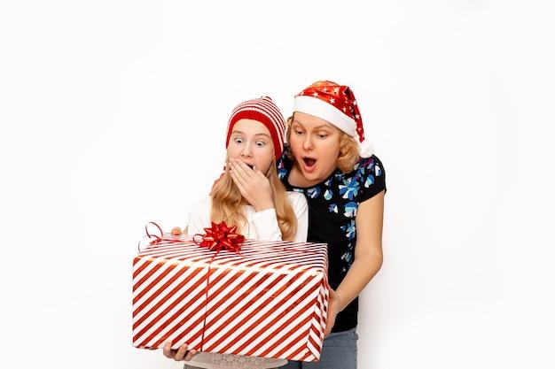 Schockierte, überraschte und glückliche mutter und tochter in weihnachtsmützen, die ein großes weihnachtsgeschenk in den händen halten