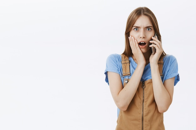 Schockierte und entsetzte frau erhalten schlechte nachrichten, während sie auf dem handy sprechen