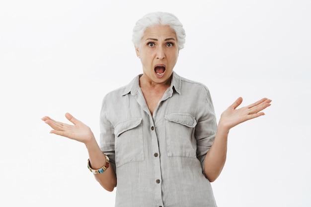 Schockierte und frustarted ältere frau, die verwirrt aussieht, kann nicht verstehen, was passiert