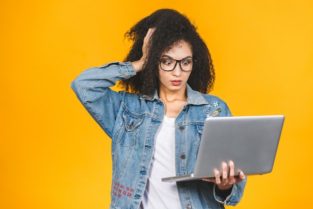 Schockierte verblüffte schwarze afroamerikaner-geschäfts- oder studentenfrau, die auf gelbem hintergrund lokalisiert aufwirft. kopieren sie den speicherplatz. arbeiten am laptop pc.