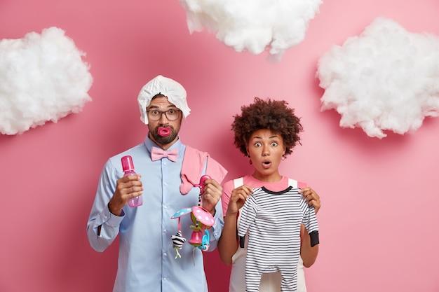 Schockierte verheiratete, vielfältige frau und mann posieren mit artikeln für neugeborene bereiten sich auf das entbindungskrankenhaus vor, bereiten sie sich darauf vor, eltern zu werden