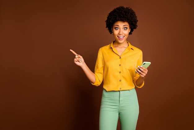 Schockierte verrückte afroamerikanische studentin verwenden smartphone punkt finger copyspace zeigen social media verkauf schreien wow tragen gelb grün trendige hosen hose isoliert braune farbe