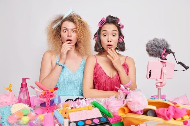 Schockierte verschiedene frauen machen frisuren tragen kleider stehen nebeneinander in der nähe eines tisches voller kosmetikprodukte nehmen sie ein video darüber auf, wie sie sich um ihr aussehen kümmern, pose vor weißem hintergrund