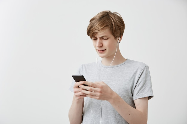 Schockierte verwirrte hipster-typ-nachrichten mit freunden, nutzt die kostenlose internetverbindung auf einem modernen handy und erhält schlechte nachrichten. erstaunter junger mann erhält schlechte nachrichten. menschliche gefühle, emotionen, reaktionen