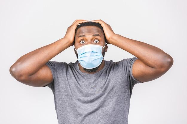 Schockierter afroamerikanermann, der hygienemaske trägt, um infektion, luftgetragene atemwegserkrankung zu verhindern