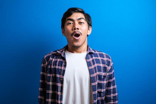 Schockierter asiatischer mann, der lässig mit offenem mund und händen gekleidet ist, schaut in die kamera. überraschter junger asiatischer studentenkerl auf blauem studiohintergrund